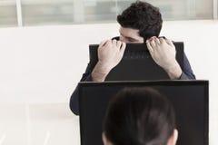 Hombre de negocios cansado que lleva a cabo su monitor de computadora y reclinación fotos de archivo