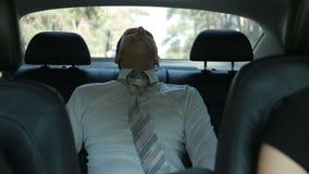 Hombre de negocios cansado que se relaja en el asiento trasero del coche almacen de video