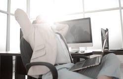 Hombre de negocios cansado que se sienta delante del escritorio imagenes de archivo