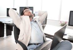 Hombre de negocios cansado que se sienta delante de su escritorio imagen de archivo