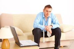 Hombre de negocios cansado que se sienta en el sofá foto de archivo