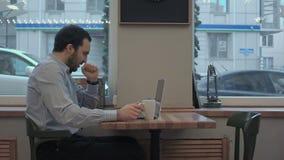 Hombre de negocios cansado que trabaja con el ordenador portátil en el café del café, del bostezo y de la consumición almacen de video