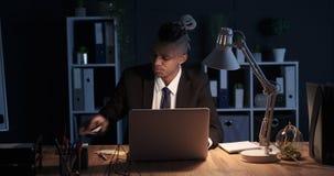 Hombre de negocios cansado que usa el ordenador portátil y el teléfono móvil en la oficina de la noche