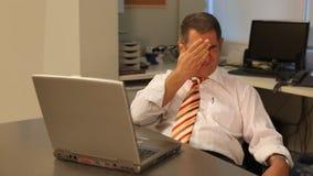 Hombre de negocios cansado usando el ordenador portátil en oficina almacen de metraje de vídeo