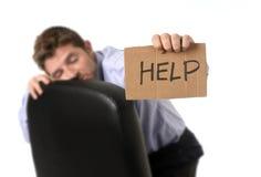 Hombre de negocios cansado y perdido atractivo joven que se sienta en la silla de la oficina que pide ayuda en la tensión imagen de archivo