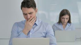 Hombre de negocios cansado Yawning en el trabajo almacen de video