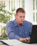 Hombre de negocios casual en oficina mientras que mecanografía en el ordenador portátil Fotos de archivo libres de regalías
