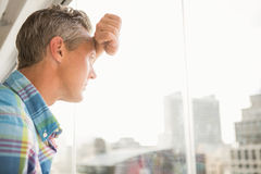 Hombre de negocios casual preocupado que se inclina contra ventana fotos de archivo libres de regalías