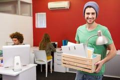 Hombre de negocios casual que lleva sus pertenencia en caja Fotografía de archivo libre de regalías