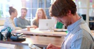 Hombre de negocios casual usando la tableta con sus colegas detrás de él metrajes