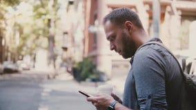 Hombre de negocios caucásico acertado confiado que se coloca en esquina de calle de la ciudad con café usando el smartphone app d metrajes