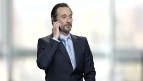 Hombre de negocios caucásico amistoso que habla en pone de la célula almacen de video
