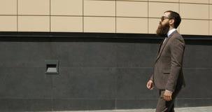 Hombre de negocios caucásico atractivo feliz que camina fuera del edificio de oficinas grande cercano y que mira alrededor Mirada metrajes