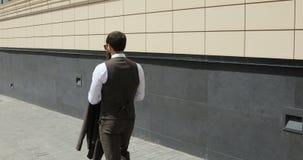 Hombre de negocios caucásico atractivo feliz que camina fuera del edificio de oficinas grande cercano y que mira alrededor Mirada almacen de video