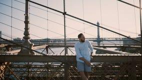 Hombre de negocios caucásico feliz que se coloca en el puente de Brooklyn, Nueva York que mecanografía en la pulsera de reloj ele almacen de metraje de vídeo