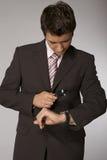 Hombre de negocios caucásico joven que mira en su reloj con magnificar Imagenes de archivo
