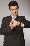 Hombre de negocios caucásico joven que mira en su reloj con magnificar Imagen de archivo