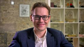 Hombre de negocios caucásico sonriente en el traje oscuro que intenta sobre sus vidrios y que sonríe directamente en la cámara en almacen de video