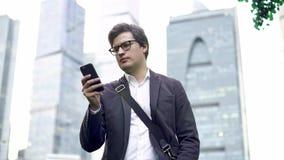 Hombre de negocios centrado en los vidrios que birlan a través de su ciudad de Moscú de la pantalla del smartphone