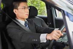 Hombre de negocios chino que conduce el coche Foto de archivo libre de regalías