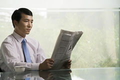 Hombre de negocios chino que lee un periódico imágenes de archivo libres de regalías