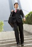 Hombre de negocios chino que recorre abajo de pasos de progresión Imagenes de archivo