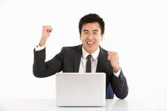 Hombre de negocios chino que trabaja en la computadora portátil y Celebra Imágenes de archivo libres de regalías