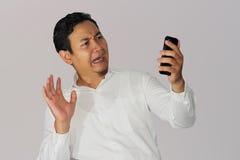Hombre de negocios chocado con el teléfono celular Fotos de archivo