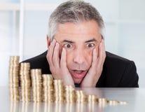 Hombre de negocios chocado con la pila de monedas imagen de archivo