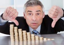 Hombre de negocios chocado con la pila de monedas fotografía de archivo libre de regalías