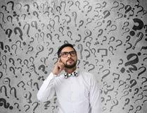Hombre de negocios chocado con los signos de interrogación Imagenes de archivo