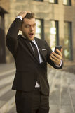 Hombre de negocios chocado que mira el teléfono celular Fotos de archivo