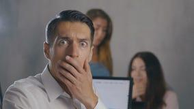 Hombre de negocios chocado y sorprendido mientras que lee un mensaje en el smartphone en el fondo de la oficina Hombre asustado c metrajes