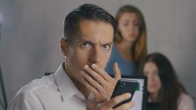Hombre de negocios chocado y sorprendido mientras que lee un mensaje en el smartphone Un hombre en sorpresa saca los vidrios y metrajes