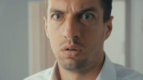 Hombre de negocios chocado y sorprendido Un hombre en vidrios de los lanzamientos de la sorpresa y miradas en la cámara en sorpre metrajes