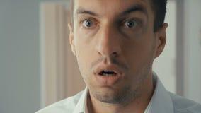 Hombre de negocios chocado y sorprendido Un hombre en vidrios de los lanzamientos de la sorpresa y miradas en la cámara en sorpre almacen de video