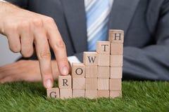 Hombre de negocios Climbing Growth Blocks en hierba Fotos de archivo libres de regalías