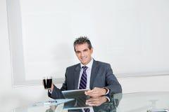 Hombre de negocios With Coffee Cup que usa la tableta de Digitaces Imagen de archivo