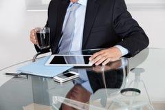 Hombre de negocios With Coffee Cup que usa la tableta de Digitaces Fotografía de archivo libre de regalías