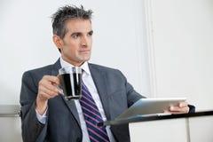 Hombre de negocios With Coffee Cup que usa la tableta de Digitaces Fotos de archivo libres de regalías