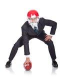 Hombre de negocios competitivo que juega a fútbol americano foto de archivo libre de regalías