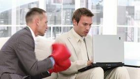 Hombre de negocios competitivo que perfora a su colega almacen de video
