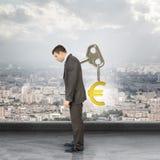Hombre de negocios con de la llave la muestra trasera y euro adentro Fotos de archivo