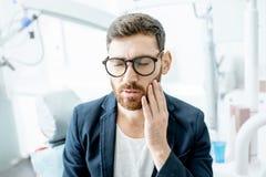 Hombre de negocios con dolor de muelas en la oficina dental fotos de archivo libres de regalías
