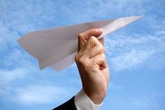 Hombre de negocios con el aeroplano de papel contra el cielo azul Fotos de archivo libres de regalías