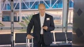 Hombre de negocios con el aeroplano que espera de la maleta en el salón de la salida del aeropuerto almacen de metraje de vídeo