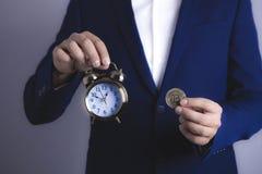 Hombre de negocios con el bitcoin y el reloj imagenes de archivo