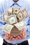 Hombre de negocios con el bolso del dinero por completo de dólares Fotos de archivo libres de regalías