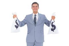 Hombre de negocios con el bolso del efectivo en cada manos fotografía de archivo