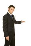 Hombre de negocios con el brazo hacia fuera en un gesto que da la bienvenida Fotografía de archivo libre de regalías